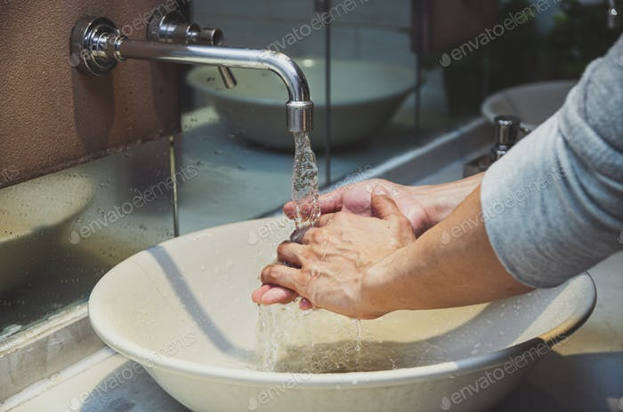 Closeup hands washing with Chrome faucet and water for Coronavirus pandemic prevention in bathroom
