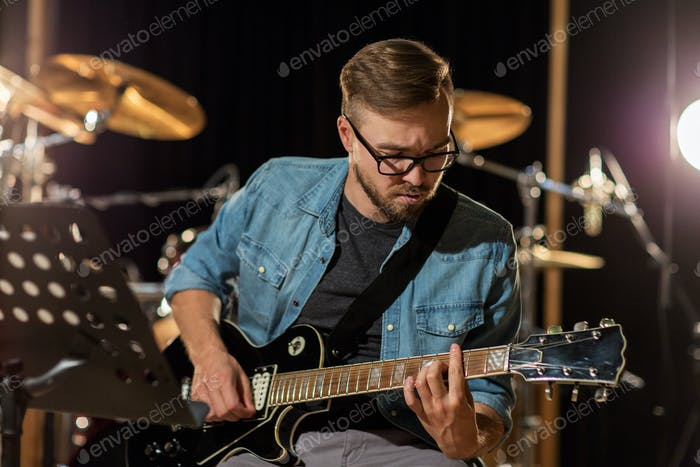 man playing guitar at studio rehearsal