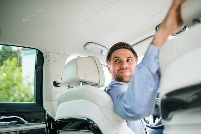 Businessman sitting in brand new car, looking back when driving