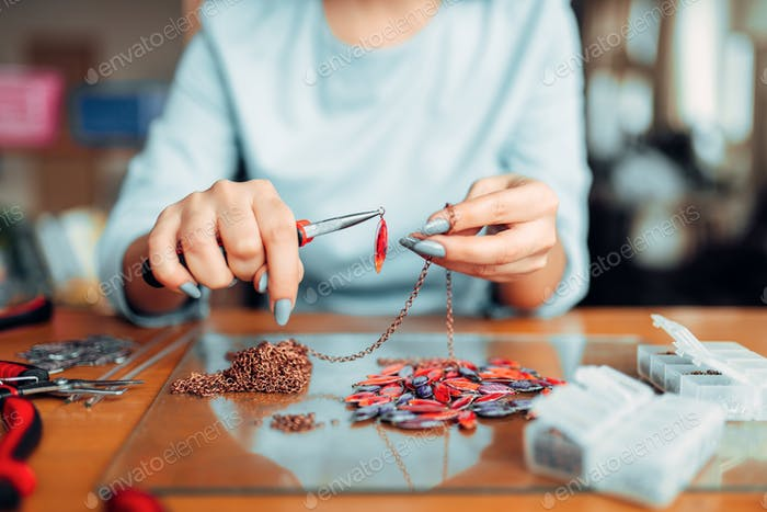 Female person holds pliers, bijouterie making