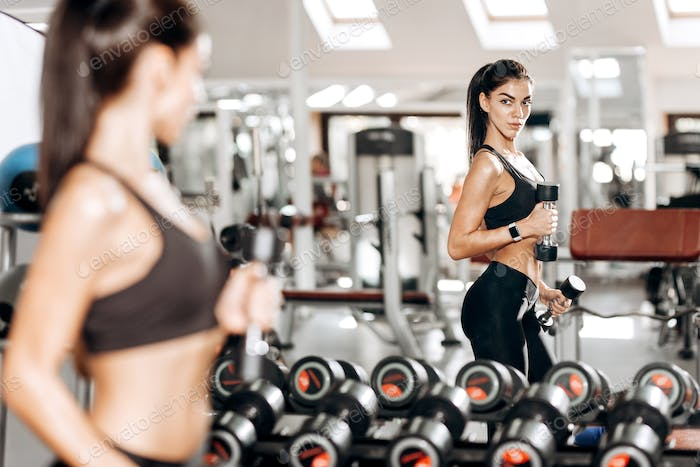 Beautiful athletic girl dressed in black sports top and tights builds up muscles with dumbbells in