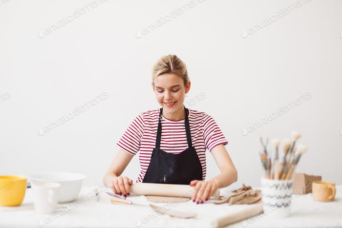 Smiling girl in black apron and striped T-shirt sitting at the table holding rolling pin
