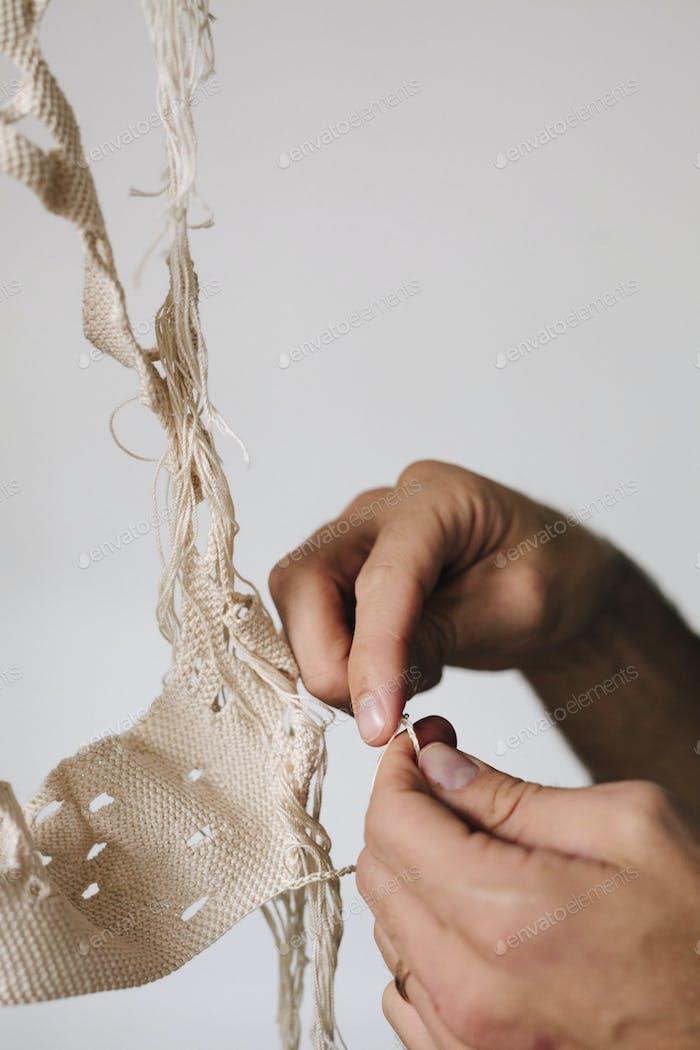 Ein Künstler, der an einem Kunstwerk arbeitet und ein Objekt mit Faden erstellt.