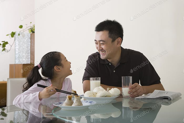 Father and daughter sat at a table