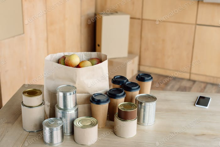canned food, disposable cups and paper bag with apples on wooden table in charity center