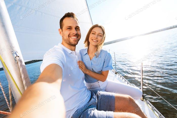 Couple Making Selfie Sitting On Deck Enjoying Sailing At Seaside