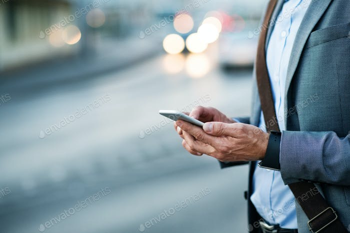 Businessman with smartphone in a city.