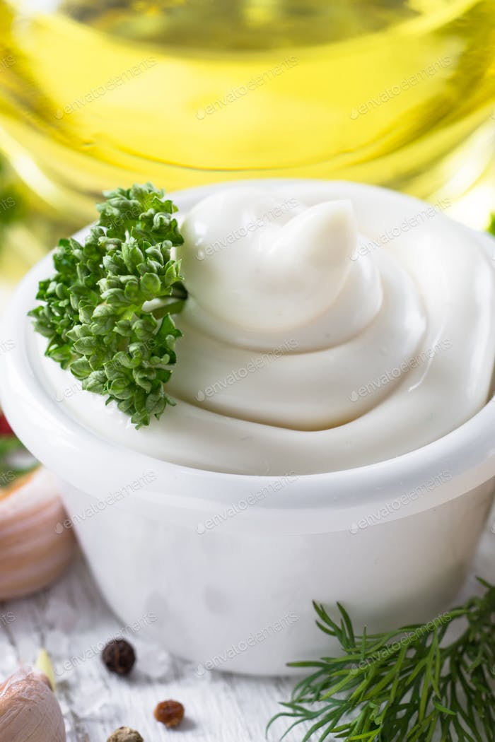 Mayonnaise sauce and ingredients on white