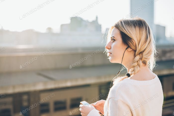 Young beautiful caucasian woman listening to music