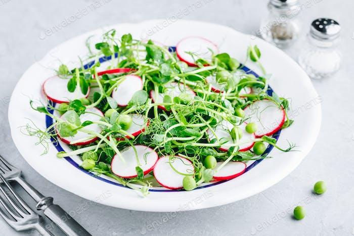 Fresh green pea shoots salad with radishes.