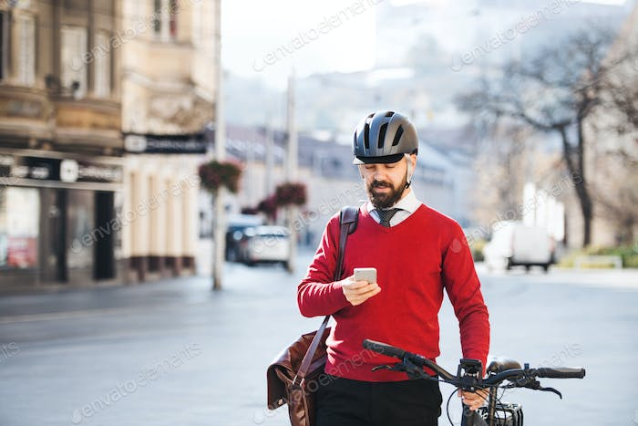 Hipster businessman commuter with bicycle and smartphone on the way to work in city.