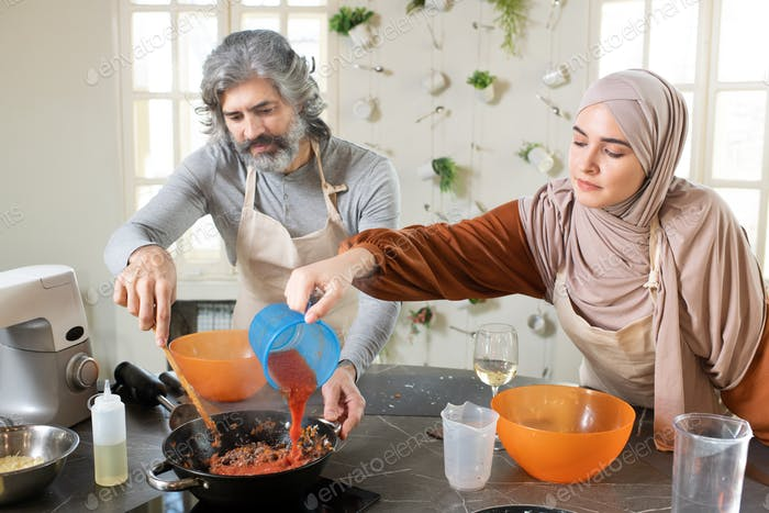 Young Muslim female in hijab pouring tomato ketchup into minced meat