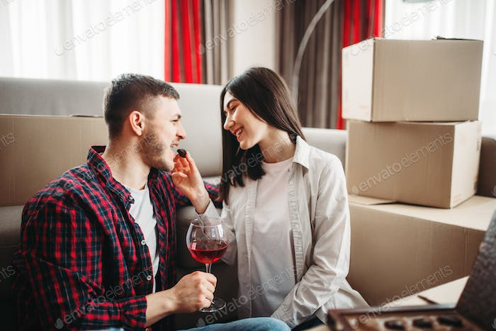 Couple drink wine, moving to new house celebration