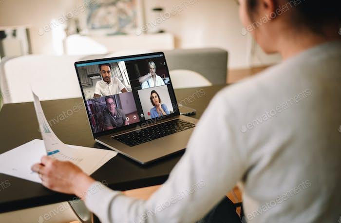Geschäftsfrau zu Hause mit einer Video konferenz mit ihrem Team