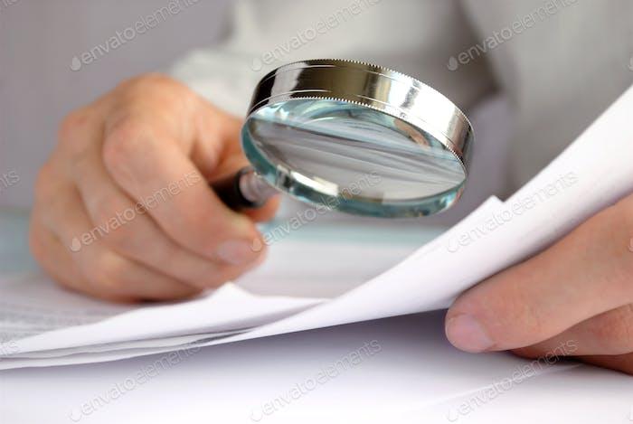 Бизнесмен, глядя через увеличительное стекло к документам