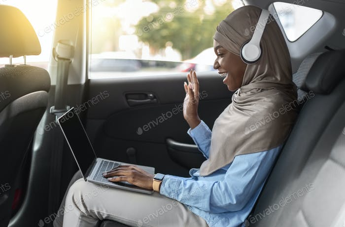 Black Islamic Lady In Hijab Making Video Call With Laptop In Car