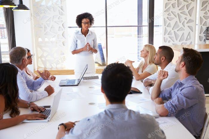 Geschäftsfrau präsentiert Kollegen bei einem Treffen