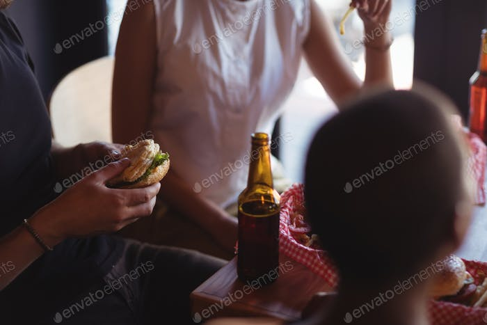 Friends interacting while having meal and beer