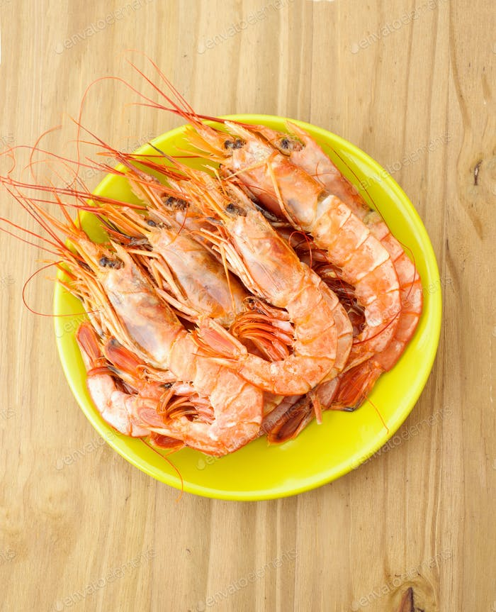 plate of raw prawns on wooden base