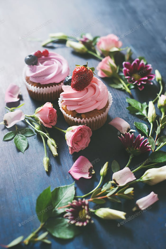 Cupcakes with strawberries and rose flowers on a dark background. Spring dessert concept with copy
