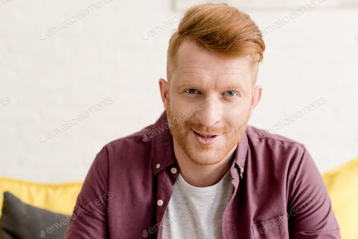 portrait of handsome young redhead man smiling at camera
