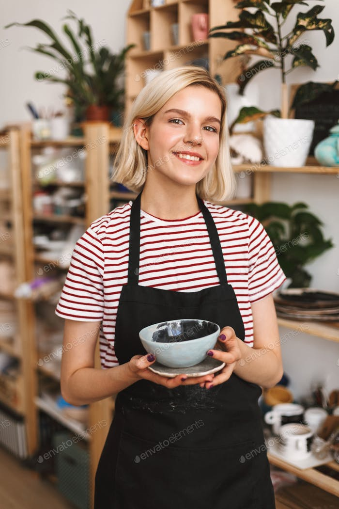 Pretty smiling girl in black apron and striped T-shirt holding handmade plate and bowl in hands