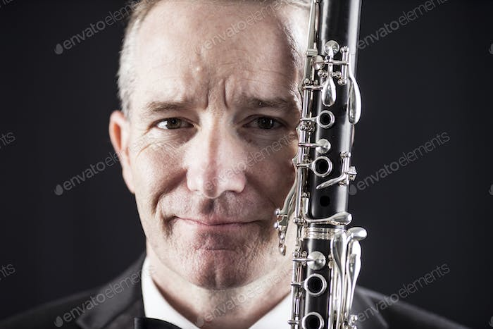 Portrait of man with clarinet over black