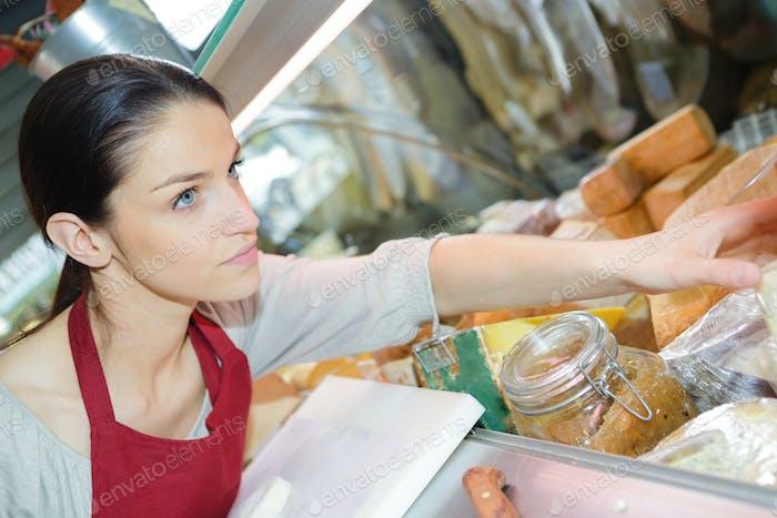 junge weibliche Kundin Verkauf von Käse zum Dessert in Delikatessenladen