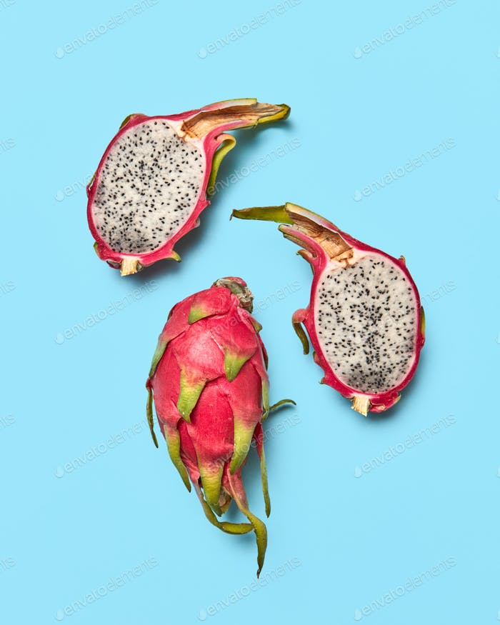 Two halves and a whole tropical fruit pitahaya presented on a blue background with copy space. Food