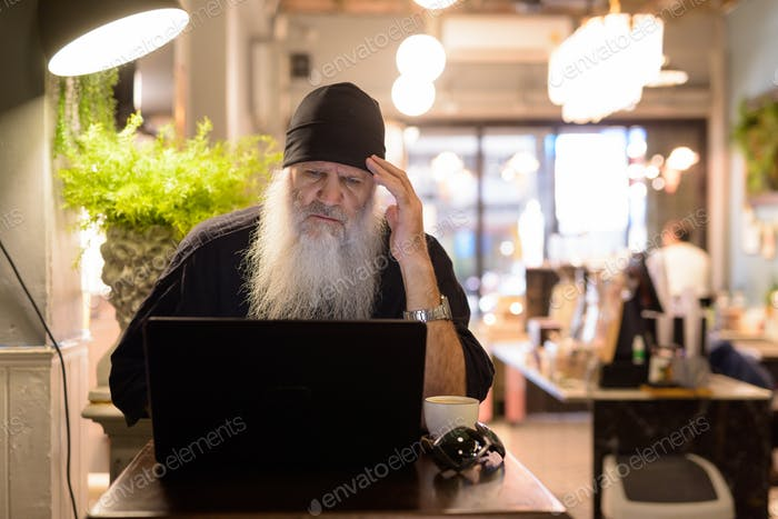 Stressed mature bearded hipster man having headache while using laptop at the coffee shop