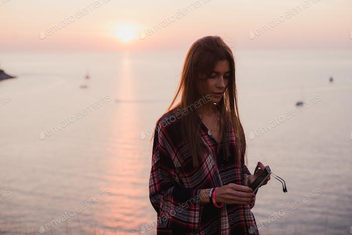 Frau SMS auf Smartphone am Strand während Sonnenuntergang