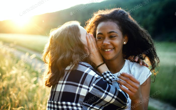 Young teenager girls friends outdoors in nature, whispering in ear