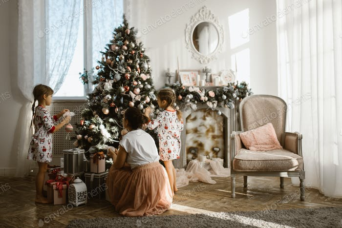 Young mother with two little daughters decorate a New Year's tre