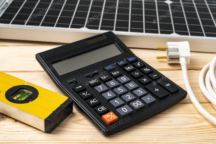 Calculator, building level and solar panel on wooden surface
