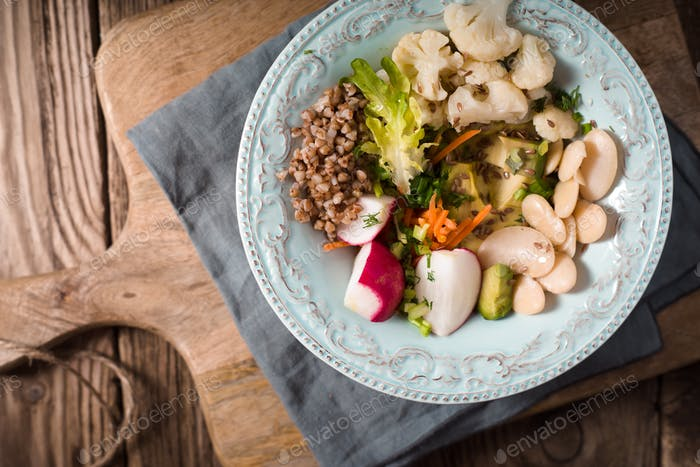 Vegetable salad with buckwheat in a turquoise blue ceramic bowl on a napkin