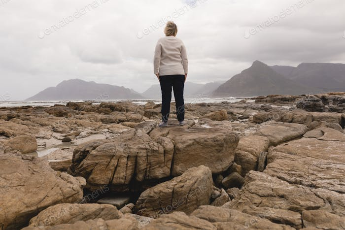 Happy senior woman standing on the rock at beach with mountains and ocean in the background
