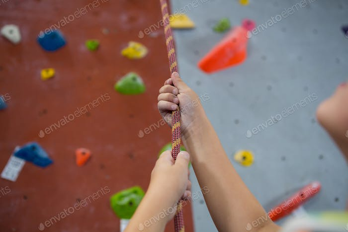 Boy practicing rope climbing in fitness studio