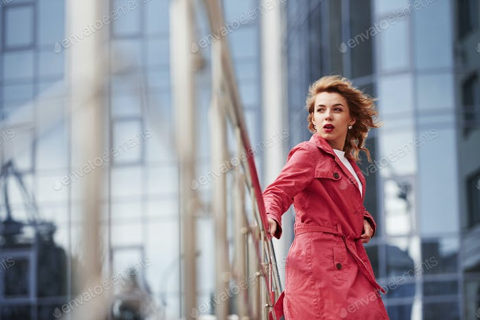 Windy day. Adult pretty woman in warm red coat have walk in the city at her weekends time