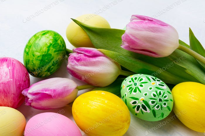 Easter background with green, yellow, pink painted eggs in the n