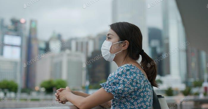 Frau tragen Gesichtsmaske und Blick auf die Stadt