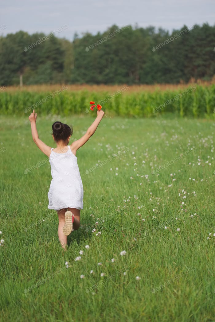 little girl with poppy in summer field
