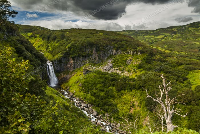 Beautiful landscape with a river and a waterfall. Kamchatka peni