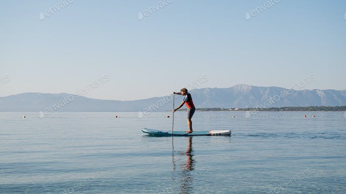 Young man in casual clothing paddling on sup board