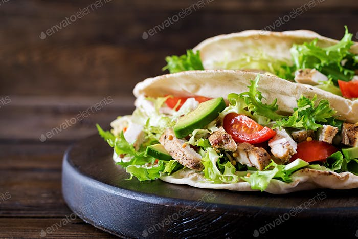 Pita bread sandwiches with grilled chicken meat, avocado, tomato, cucumber and lettuce served