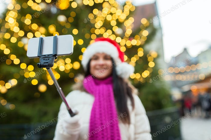 woman taking selfie with smartphone at christmas