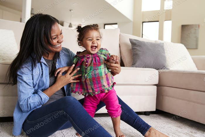 Mother Playing With Baby Daughter Sitting On Floor Of Lounge At Home