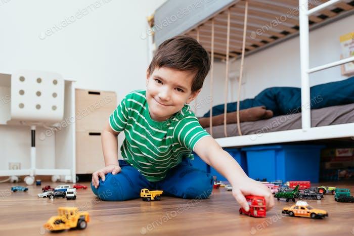 Niedlicher Junge spielt mit rotem Doppeldecker in der Hand.