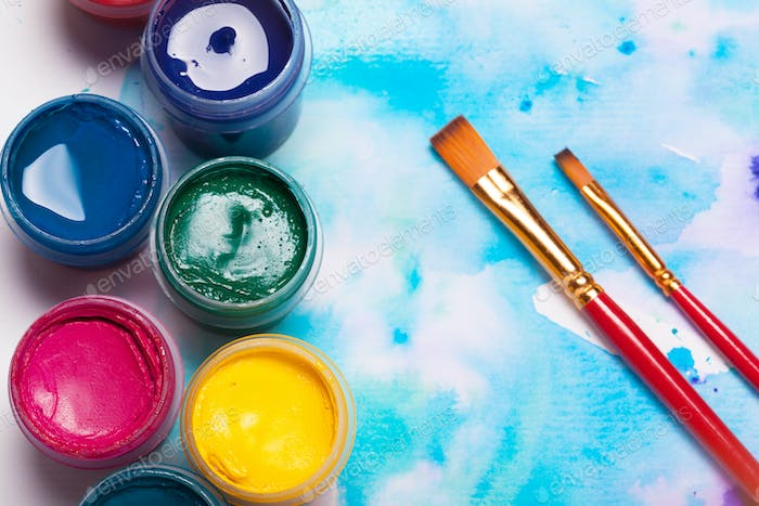 Top view of work process of watercolor paper pad, watercolor painting supplies and brushes