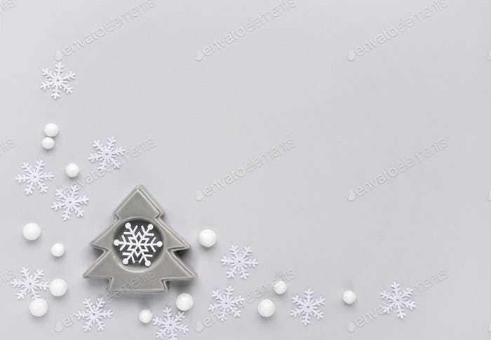 Snowflakes and decorative spruse on gray background