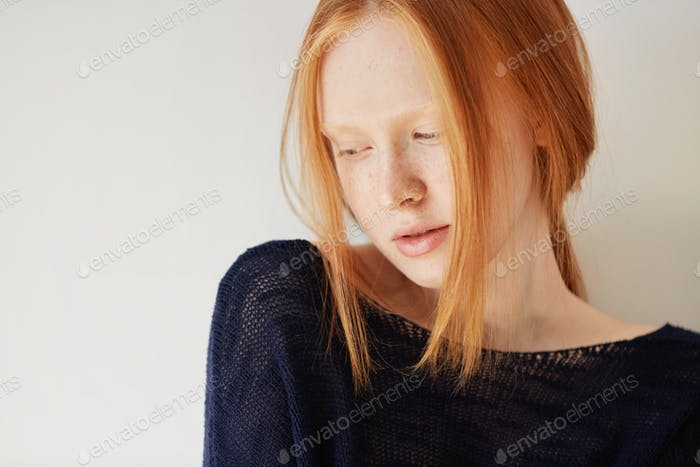 Beautiful female teenage model wearing casual black top looking down with shy and thoughtful express